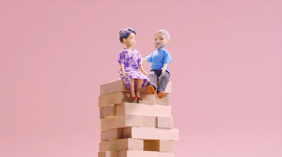 A composite of an elderly doll couple on a jenga tower for CPF Board's social media campaign on retirement planning