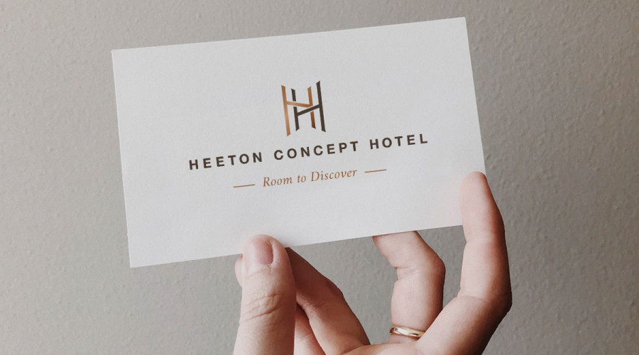 """A Heeton Concept Hotel logo and tagline that reads """"Room to Discover"""" on a business card"""