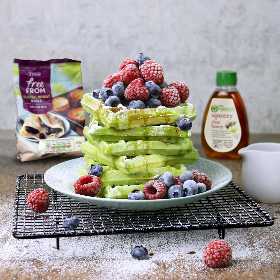 A stack of pandan waffles topped with berries, accompanied by Tesco products used to make the dish